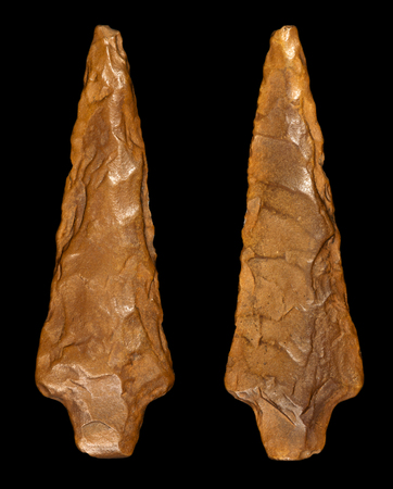 arrowhead: Macro photography of a prehistoric arrowhead in flint stone. Front and back, isolated on black background