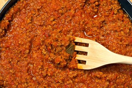 Detail der italienischen Fleischsoße (Soße oder Ragu von Bolognese) kochte mit Fleisch, Gemüse und Tomatensauce, mit einer hölzernen Gabel