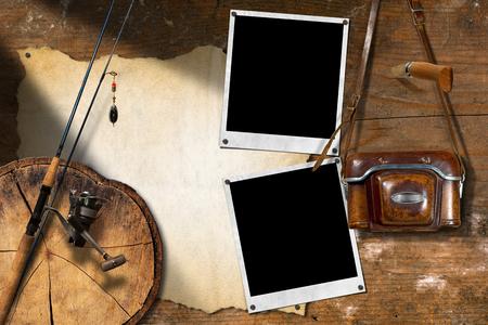 temperino: Attrezzatura da pesca, macchina fotografica d'epoca, due vuoti cornici per foto istantanee, temperino e pergamena vuoto su un muro di legno Archivio Fotografico
