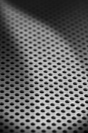 latticed: Detail of a metallic background with round holes and shadows