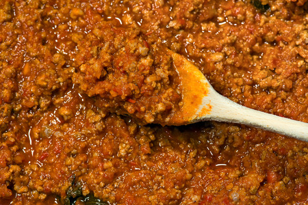 meat sauce: Detail of italian meat sauce (Bolognese sauce or ragu) cooked with meat, vegetables and tomato sauce, with a wooden spoon