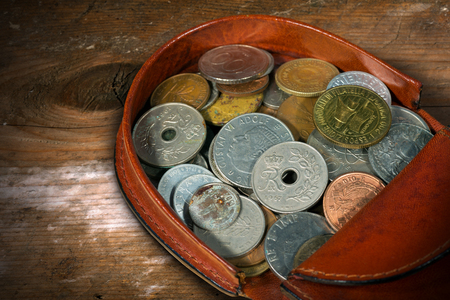 coin purse: Macro photography of a brown leather coin purse with old and vintage coins. On a wooden table Stock Photo