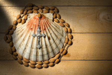 atone: Scallop seashell and wooden rosary beads with a silver crucifix on a wooden background. Symbols of Christian pilgrimage