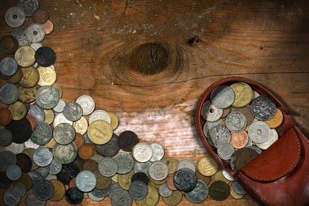 antique coins: Brown leather coin purse with old and vintage coins. On a wooden table with many antique coins