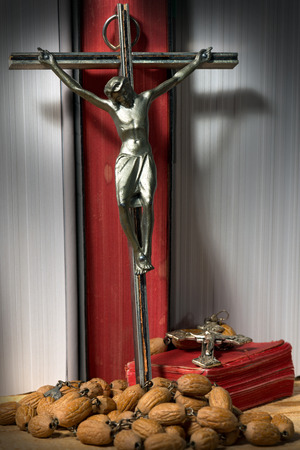 crucifixes: Two silver crucifixes, two Holy Bibles with red pages and a wooden rosary beads in a library with books with white paper