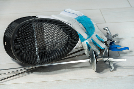 fencing foil: Fencing foil equipment. Three fencing foils with pistol grip (sporting weapon), a fencing mask and a blue and white glove on floor Stock Photo
