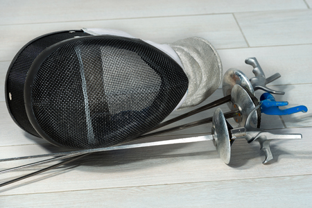 sporting equipment: Fencing foil equipment. Three fencing foils with pistol grip (sporting weapon) and a fencing mask on a floor Stock Photo