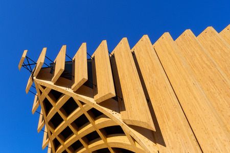 rafter: Detail of a modern wooden architecture in glued laminated timber on a blue sky