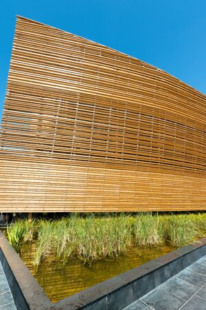 wood grass: Close up of a modern wooden architecture with green grass and water Editorial