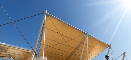 roofing membrane: Detail of a modern tensile structure, membrane fabric roof with poles and steel cables, on a blue clear sky with sun rays