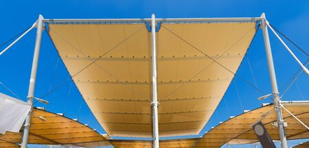 roofing membrane: Detail of a modern tensile structure, membrane fabric roof with poles and steel cables, on a blue clear sky