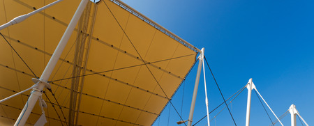 membrane: Detail of a modern tensile structure, membrane fabric roof with poles and steel cables, on a blue clear sky