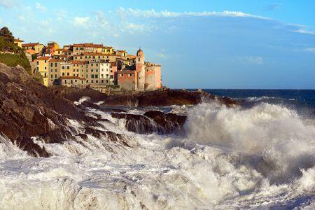 george: Tellaro village with the Church of St. George (San Giorgio), with cliffs and white sea waves. La Spezia, Liguria, Italy Stock Photo