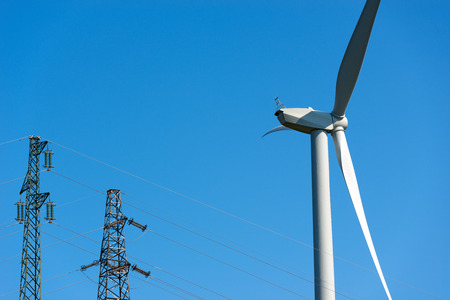 powerline: Detail of a white wind turbine with a power line (two high voltage towers) on a clear blue sky