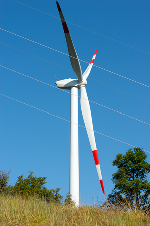 powerline: White and red wind turbine with a power line (high-voltage cables) on a clear blue sky Stock Photo