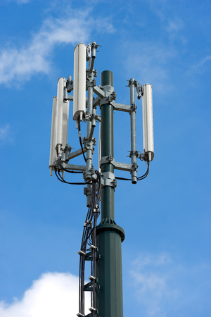 Detail of a telecommunications tower (cell phone) with blue sky and clouds Stock Photo