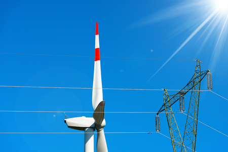 powerline: Detail of a white and red wind turbine with a power line and sun rays on a clear blue sky