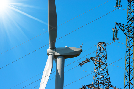 powerline: Detail of a white wind turbine with a power line and sun rays on a clear blue sky