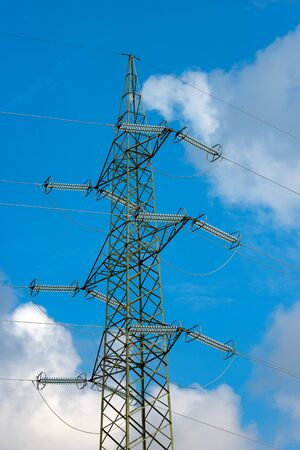 Detail of a high voltage tower (power line) with electric cables and insulators, on a blue sky with clouds Stock Photo