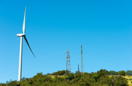 powerline: White wind turbine over a green hill with a power line on a clear blue sky Stock Photo