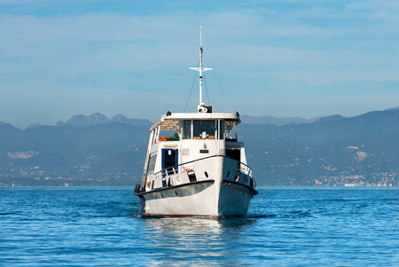 lake front: Ferry boat during navigation in front of the town of Lazise in the Garda Lake, Veneto, Italy. In the background the coast of Lombardy