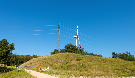 powerline: White and red wind turbine over a green hill with a power line on a clear blue sky