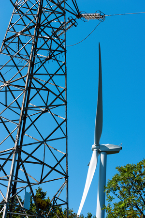 powerline: Detail of a white wind turbine with a power line on a clear blue sky