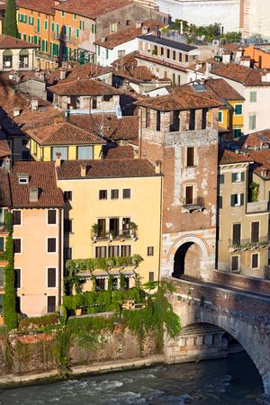 1st century: The tower of the Ponte Pietra (Stone bridge) - 1st century B.C. - the oldest Roman monument in Verona (UNESCO world heritage site) and the Adige river, Veneto, Italy