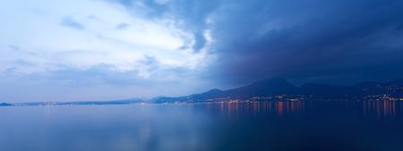 maderno: Lago di Garda at night (Garda Lake), the largest Italian lake of glacial origin with the lights of the coast of Lombardy, Italy Stock Photo