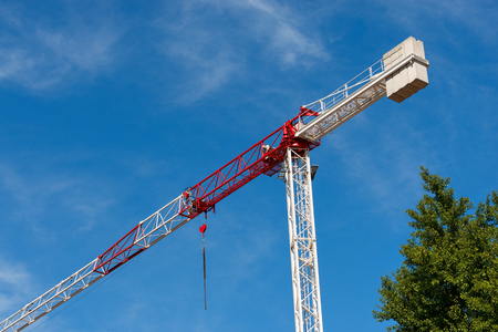 Detail of a red and white crane on blue sky with clouds and a green tree. Construction site Stock Photo