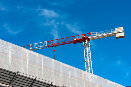 safety net: Detail of a construction site with red and white crane and a scaffolding with a white safety net on blue sky