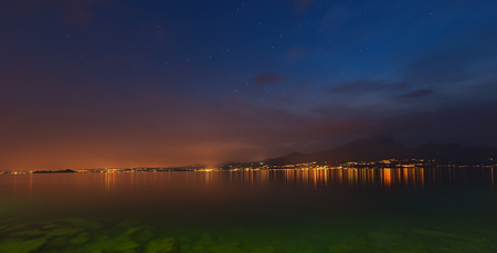 maderno: Lago di Garda at night (Garda Lake), the largest Italian lake of glacial origin with the lights of the coast of Lombardy and starry sky, Italy