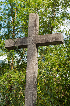 Detail of a grey marble Christian cross with green trees. Trentino Alto Adige, Italy