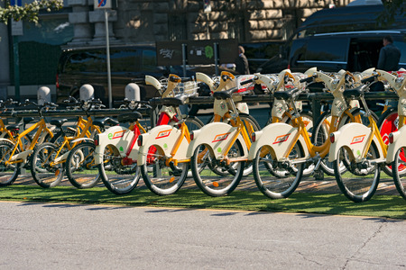 mi: MILANO, ITALY - SEPTEMBER 24, 2016: City bikes for rent parked in Milan, Lombardy, Italy. Bike sharing service operated by the bikeMi company Editorial
