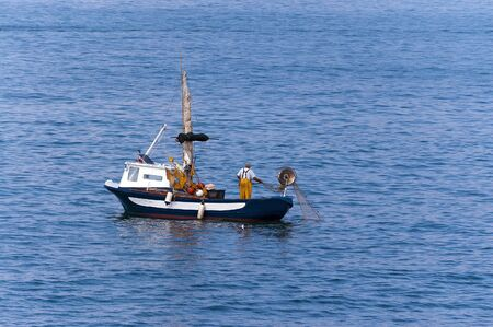 Fisherman on a small blue and white boat with fishing net between the waves of the sea. Liguria, Italy