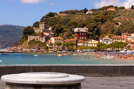 The village of  San Terenzo (St. Terenzo) with the beach crowded with sunbathers. Lerici, in the Gulf of La Spezia, Liguria Italy