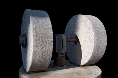 squeeze shape: An old olive press with two millstones isolated on a black background, Veneto, Garda lake, Italy Stock Photo