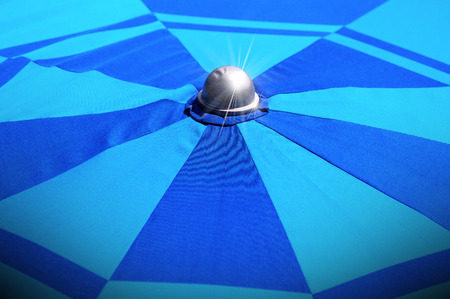holidaying: Detail of the top of a blue beach umbrella (sunshade - parasol) with sparkles