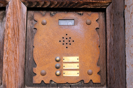 interphone: Detail of an old rusty interphone with three doorbell buttons and video camera, on a wooden door. Verona, Italy Stock Photo