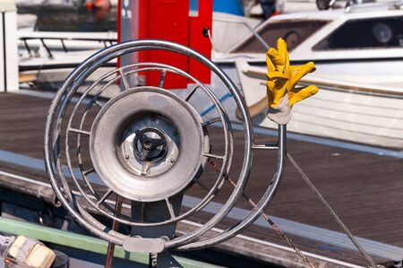 work boat: Detail of a fishing boat with a metallic winch for fishing net with ropes and yellow  work gloves