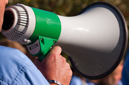 superintendent: Detail of a scout leader shouting through a green and white megaphone