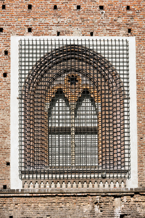 xv century: Detail of an ancient window with grating in wrought iron of the Sforza Castle XV century (Castello Sforzesco) in Milano, Lombardy, Italy