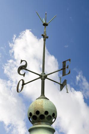 puntos cardinales: puntos cardinales de edad (puntos cardinales norte, este, sur, oeste) en una azotea con un pararrayos en el cielo azul con nubes