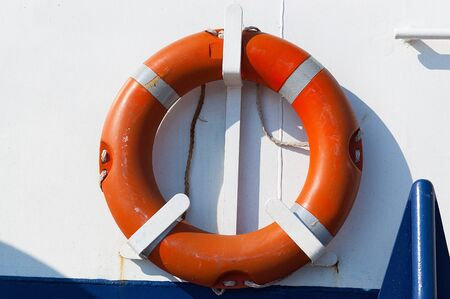 lifebuoy: Detail of an old orange lifebuoy on a white and blue passenger ship