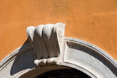 keystone: Detail of an old stone arch with ancient keystone on an orange wall. Verona, Veneto, Italy, Europe Stock Photo