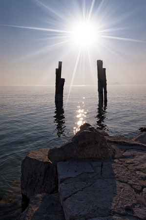 bollards: Wharf on the Garda Lake (Lago di Garda - Punta San Vigilio) with sun rays (backlight) and silhouette of wooden bollards. Italy