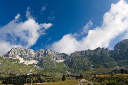 high plateau: The high Plateau of Montasio with green pastures in summer and Julian Alps (Jof di Montasio). Udine, Friuli Venezia Giulia, Italy, Europe