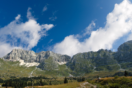 The high Plateau of Montasio with green pastures in summer and Julian Alps (Jof di Montasio). Udine, Friuli Venezia Giulia, Italy, Europe