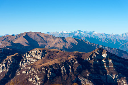 high plateau: Italian alps in Veneto and Trentino. In the foreground the Monte Baldo (Baldo Mountain) and in the background the group of Adamello seen from the plateau of lessinia