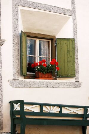 window bench: Typical window with pot of geraniums, wooden shutters and bench. Guarda Village, Swiss Alps. Scuol, Engadine, Switzerland